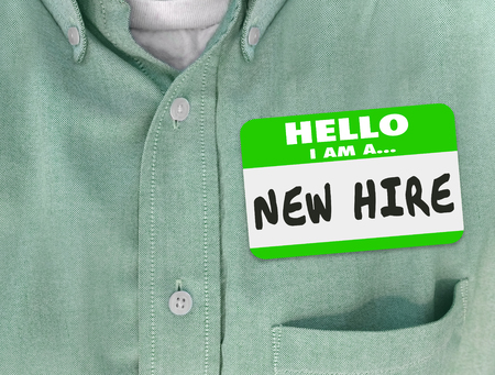employee: New Hire nametag on a green shirt worn by a new employee or fresh talent just brought onboard to a company or business Stock Photo