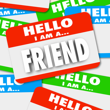companions: Friend word symolizing friendship on a nametag sticker in a pile of name tag badges Stock Photo