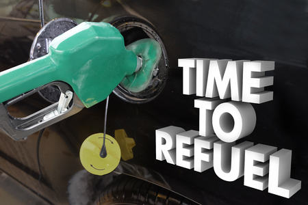 lacking: Time to Refuel words in 3d letters next to a gas nozzle filling a car or trucks gasonline tank with power