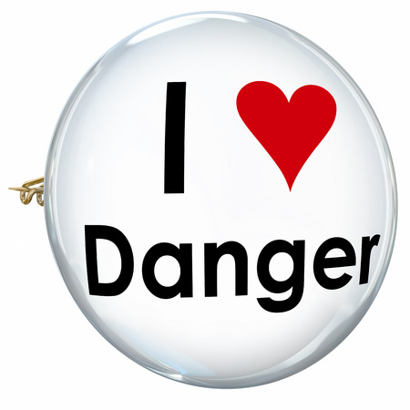 behaving: I Love Danger words and heart on a pin or button to illustrate someone who is reckless, foolish, a daredevil or thrill seeker and wants constant adventure in life