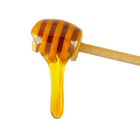 Honey dripping from a wooden honey dipper isolated on white background