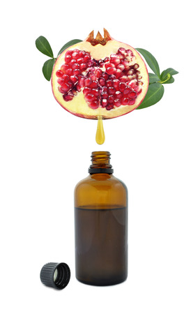 Fresh pomegranate oil flowing from pomegranate into the bottle Stock fotó