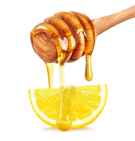 honey dripping on a slice of lemon on a white background 스톡 콘텐츠