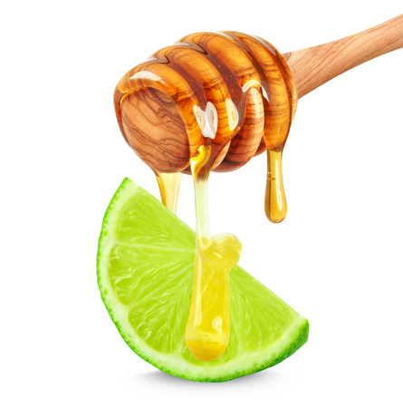 honey dripping on a slice of lime on a white background