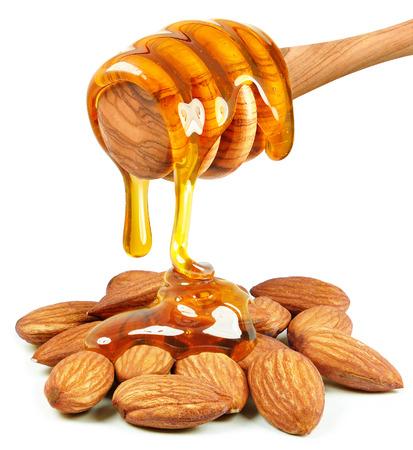 Druipen honing amandel noten op een witte achtergrond