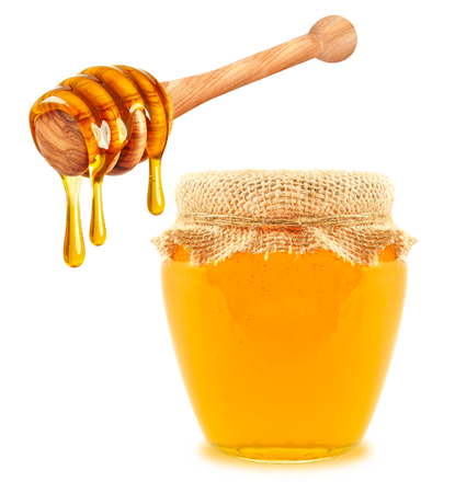 honey in a jar and a dripper on a white background