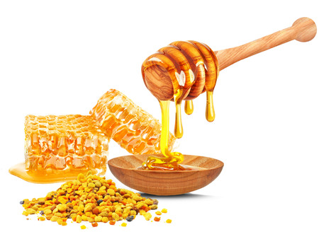 honey dripping in a bowl, honeycomb and bee pollen isolated on a white background