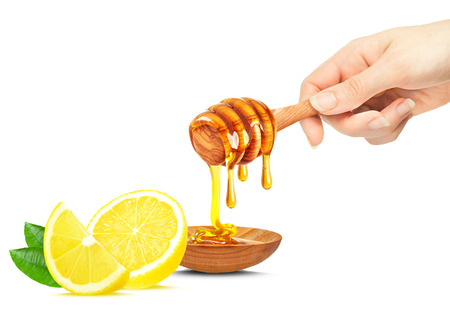 honey dripping in a bowl, lemon and hand isolated on white Stock fotó