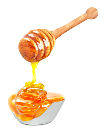 honey dripping into a bowl isolated on white