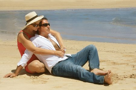 Romantic couple sitting on the sandy beach in the vacation