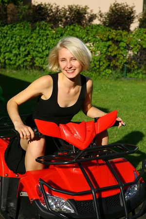Portrait of a beautiful young lady on the all-terrain vehicle (ATV) photo