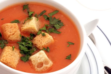 Tomato soup with croutons in ceramic bowl on white photo