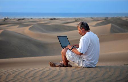 Man sitzt mit Laptop in der Wüste. Lizenzfreie Bilder