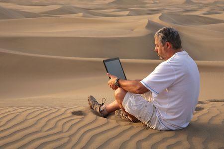 Mann mit Laptop sitzen in der Wüste.