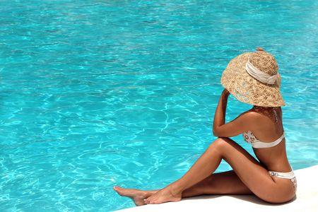 Frau mit Hut Entspannung am Pool Lizenzfreie Bilder