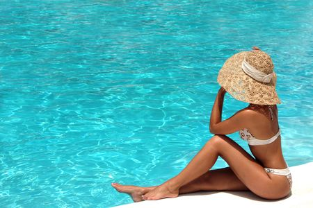 colorfully: Woman in hat relaxing beside the pool
