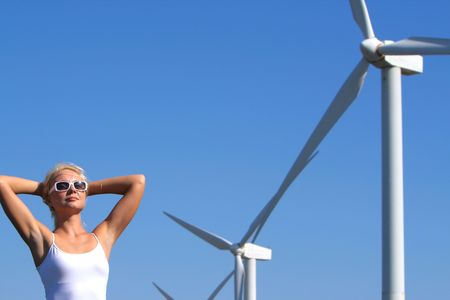young woman dreams about the future on a wind farm beneath eolic generator Standard-Bild