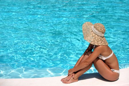 Woman in hat relaxing beside the pool photo