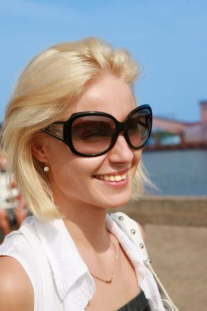 Young woman in sunglasses on  sea port photo