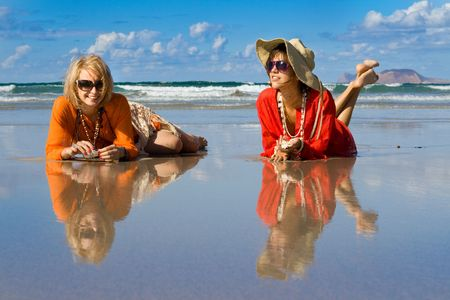 two beautiful women lays on beach photo