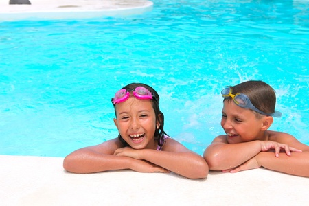 Happy children,  girl and boy, relaxing on the side of a swimming pool wearing pink and grey goggles photo