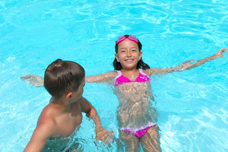 Happy children,  girl and boy, relaxing on the side of a swimming pool wearing pink and grey goggles Stock Photo - 10037073