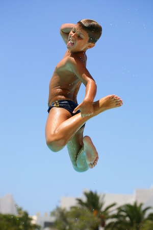 little boy swimming: boy jumping into the pool smiling  Stock Photo