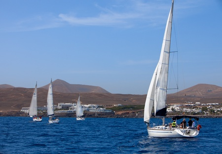 LANZAROTE, SPAIN - OCTOBER 11: three fully crewed yachts out sailing with white sails   on Russian BOSS Regatta,  9-16 October 2011, Canarian island, Spain