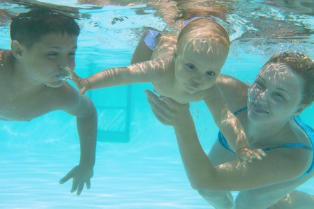 swim goggles: Underwater family in swimming pool. Mother teaching her kids  Stock Photo