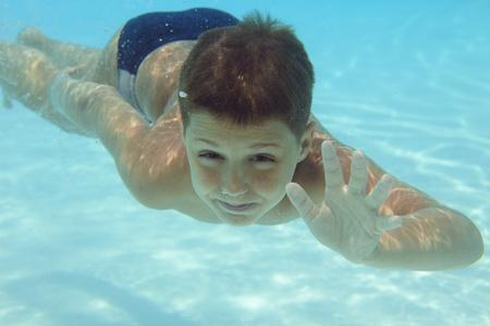 Boy swimming underwater in swimming pool  Stock Photo