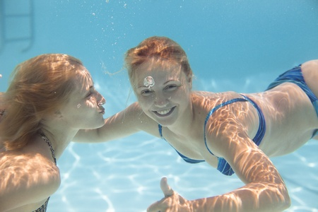 girl swimming: young woman swimming  Under wate rwith joy Stock Photo