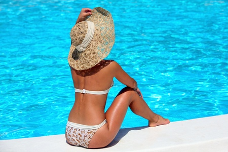 beside: Woman in hat relaxing beside the pool  Stock Photo