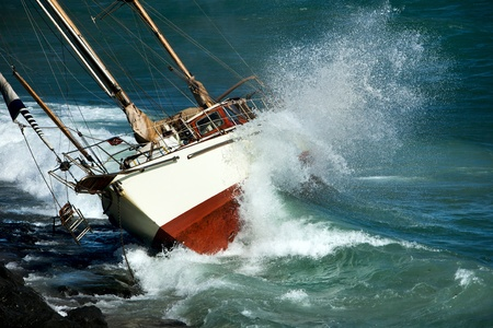 yacht crash on the rocks in stirmy weather Foto de archivo