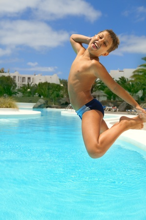 boy jumping into the pool smiling