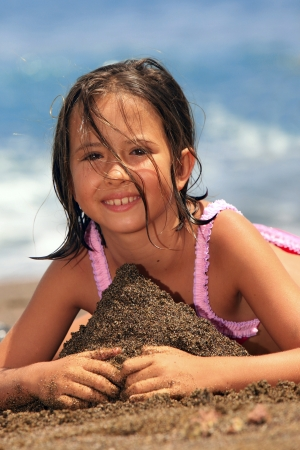 little girl sitting: girl in the beach Stock Photo