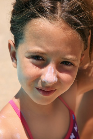 nouse: cute girl sunbathing with sunscreen in her nouse at the beach  Stock Photo