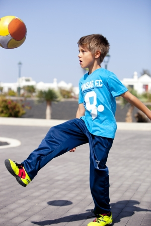 A boy playing football in the street photo