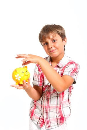 vertica: boy puts the coin into the piggy bank isolated on white