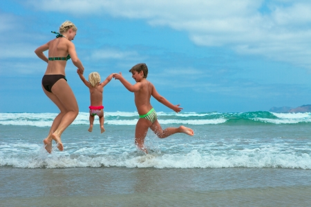 Mother and two kids  jumping on beach