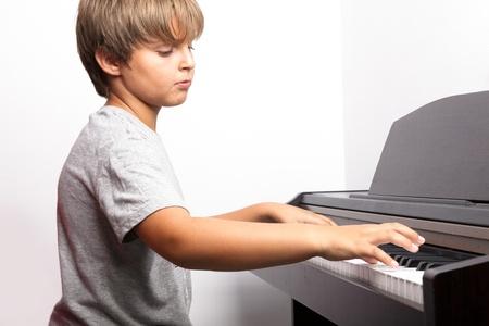tocando piano: Chico joven a tocar el piano Foto de archivo