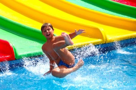 Niño en la diapositiva de agua en parque acuático Foto de archivo