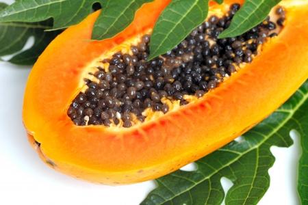 Reife Papaya mit Samen und grünen Blättern auf einem weißen Hintergrund