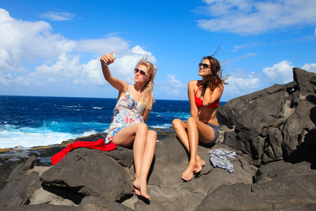 two girls taking photo on the beach in summer holidays and vacation photo