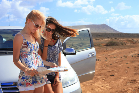 Two young women with car look at road map with mountain landscape in background