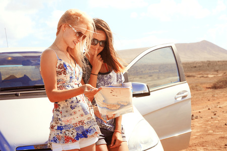 Two young women with car look at road map with mountain landscape in background photo