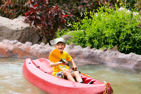 Happy boy paddling kayak on the river and enjoying a lovely summer day  photo