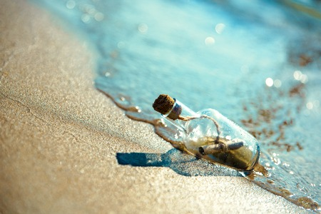 A bottle with a message is thrown by a wave on a sandy beach. Sandy background. The bottle floats in the surf line.