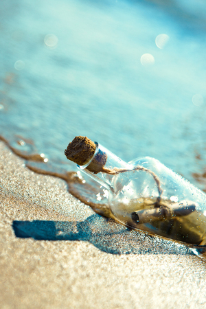 A bottle with a message is thrown by a wave on a sandy beach. Sandy background. The bottle floats in the surf line