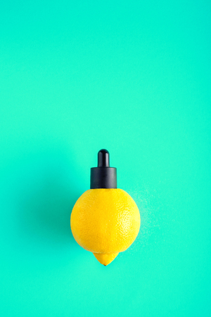Metaphor, bottle with whey, butter in lemon. The concept of vitamin C in cosmetics and aromatherapy.