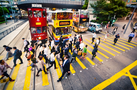 HONG KONG, CHINA - APRIL 29, 2014: crowd of people in business suits cross the road on a pedestrian crossing. View from above